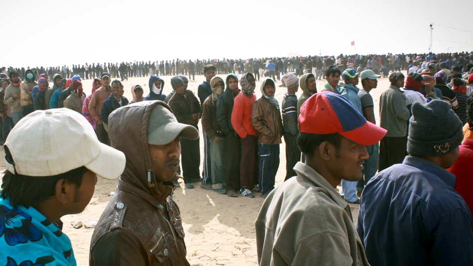 """Tunisia, Shousha camp. Third-country nationals lining up for food"""