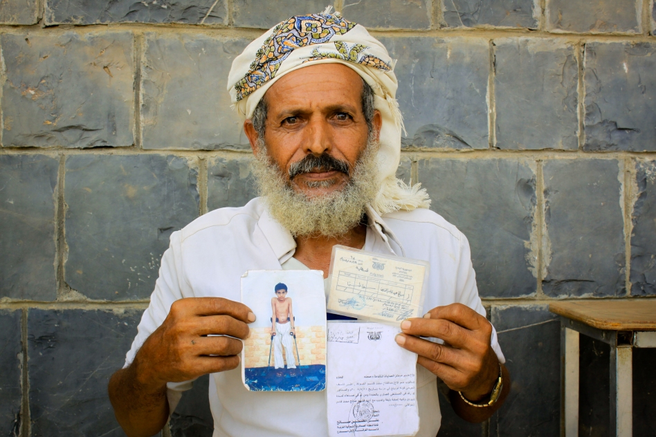 """Yemen, Al Mazrak camp. Displaced Yemeni showing the photo of his son who died in the war"""