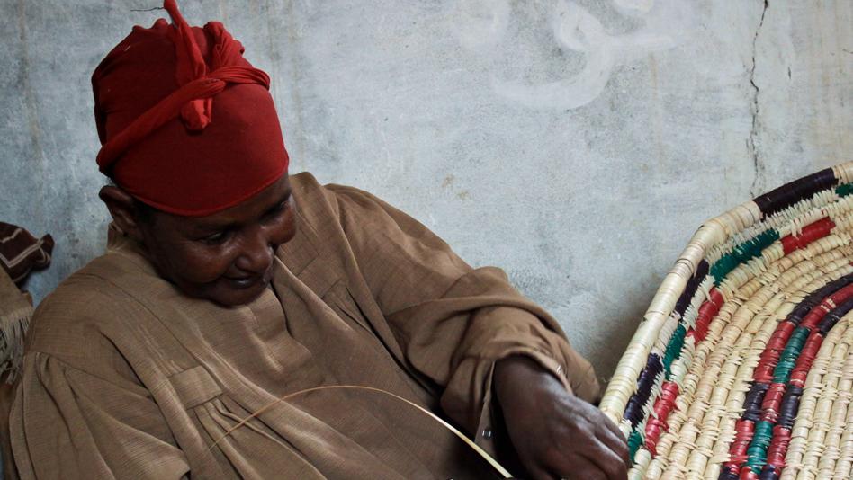 """Yemen, Kharaz camp. Somali refugee making a straw basket"""